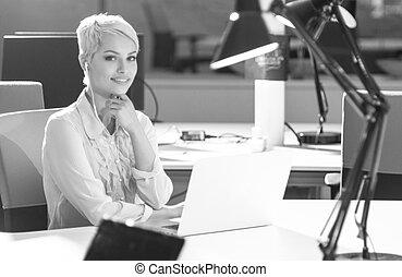 Businesswoman using laptop at work