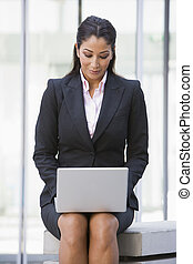 Businesswoman using laptop computer outside