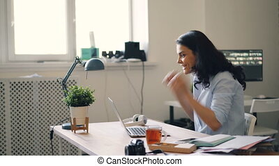 Businesswoman using laptop getting good news clapping hands...