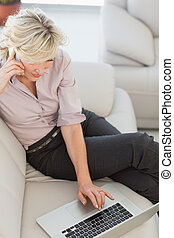 Businesswoman using laptop in living room