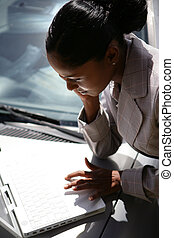 Businesswoman using laptop on her car bonnet