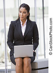 Businesswoman using laptop outside