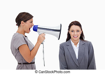 Businesswoman using megaphone to yell at colleague against a...