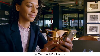 Businesswoman using mobile phone in office cafeteria 4k
