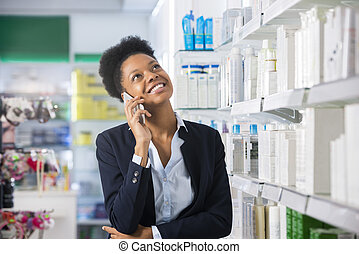 Businesswoman Using Mobile Phone In Pharmacy
