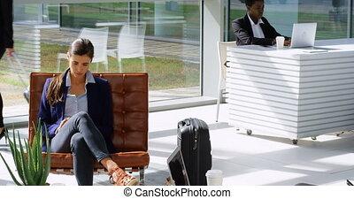 Businesswoman using mobile phone on sofa 4k