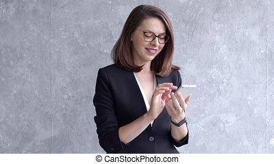Businesswoman using mobile phone, writing email or text ...