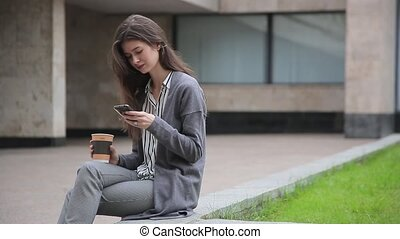 businesswoman using smart phone, drinking coffee, seating outside