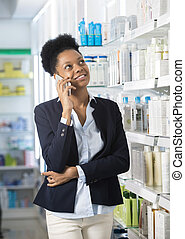 Businesswoman Using Smart Phone In Pharmacy