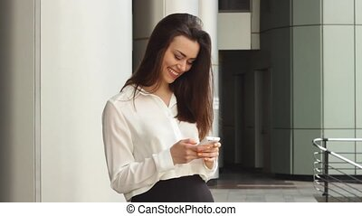 Businesswoman using smartphone on street - Young female in...