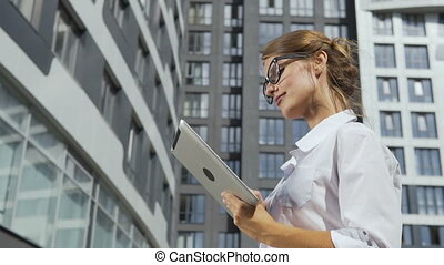 Businesswoman Using Tablet in front of Corporation