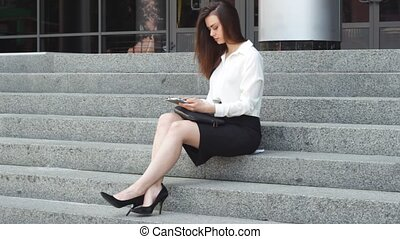 Businesswoman using tablet on steps - Pretty young woman in...