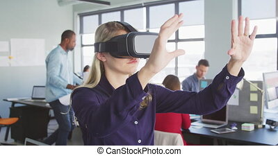 Side view of a blonde haired Caucasian female business creative working in a casual modern office, sitting at a desk using a VR headset and touching virtual interactive screen, with colleagues working in the background in slow motion