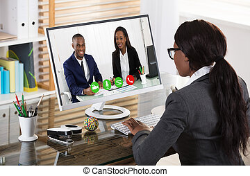 Businesswoman Videoconferencing With Her Colleagues On Computer