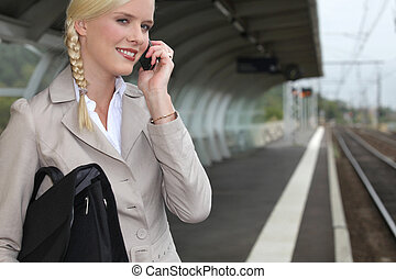 Businesswoman waiting for a train at the station