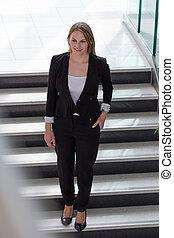 Businesswoman walking down stairs