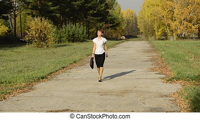 Businesswoman walking in the autumn park with a bag
