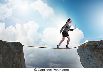 Businesswoman walking on tight rop in business concept