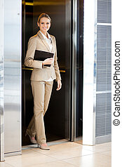 businesswoman walking out elevator - beautiful young...