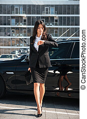 Businesswoman walking outdoors and looking at wristwatch