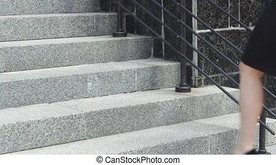 Businesswoman walking up building steps - Crop woman in suit...