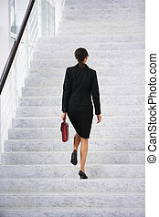 Businesswoman walking up steps