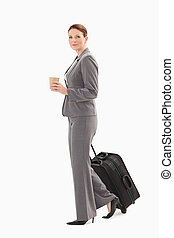 Businesswoman walking with coffee and suitcase