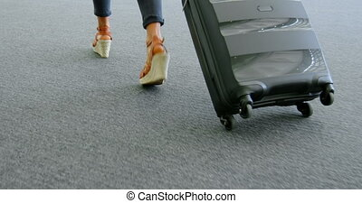 Businesswoman walking with suitcase in office 4k