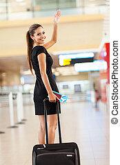 businesswoman waving goodbye at airport
