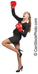 Businesswoman wearing boxing gloves expressing rapture....