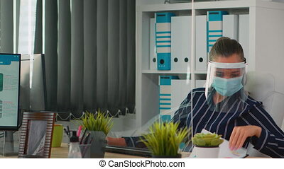 Businesswoman wearing face protection in prevention for coronavirus typing on computer working in new normal office. Freelancer working in financial company respecting social distance during covid-19
