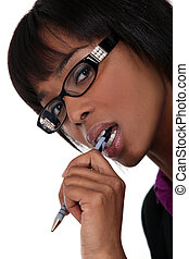 Businesswoman wearing glasses and chewing a pen