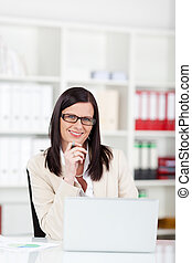 Businesswoman wearing glasses with a laptop