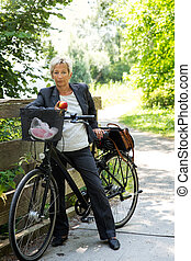 Businesswoman with a bike in the nature