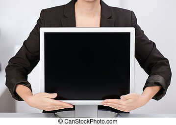 Businesswoman with a blank computer monitor