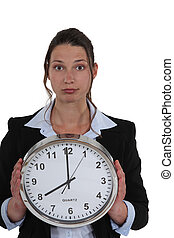 Businesswoman with a clock showing 8am