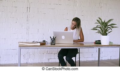 Businesswoman with a laptop in her office, working.