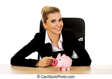 Businesswoman with a piggybank behind the desk