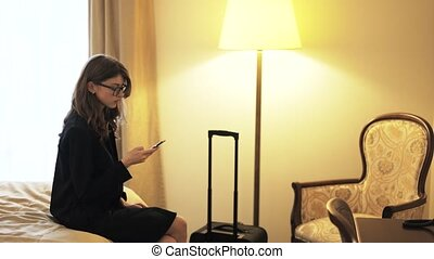 Businesswoman with a smartphone leaving a hotel room