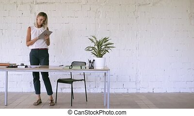 Businesswoman with a tablet in her office, working.