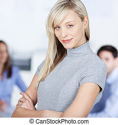 Businesswoman With Arms Crossed Against Colleagues In Office