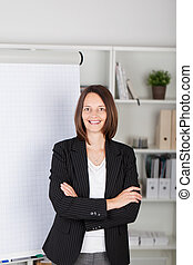 Businesswoman With Arms Crossed Standing Against Flipchart