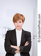 Businesswoman With Arms Crossed Standing In Office