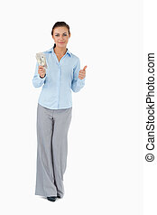 Businesswoman with banknotes giving thumb up