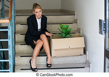 Businesswoman With Belongings Sitting On Steps At Office