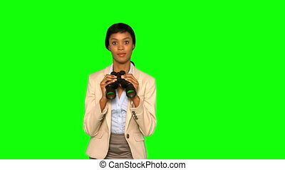 Businesswoman with binoculars jumping on green background