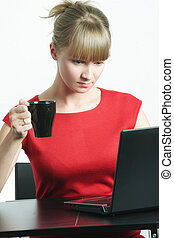 Businesswoman with black cup looking to monitor