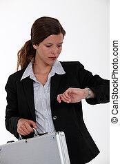 Businesswoman with briefcase checking watch
