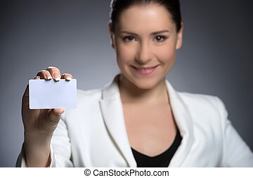 Businesswoman with business card. Confident middle-aged woman in formalwear holding business card and smiling while isolated on grey