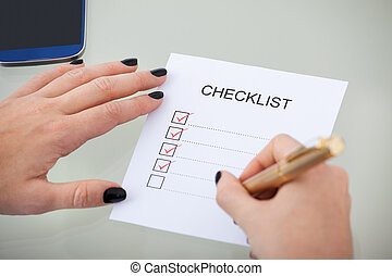 Businesswoman With Checklist At Desk